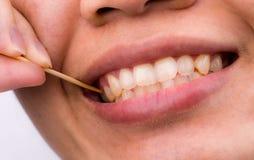 亚裔妇女从食物清洗她的牙在早餐,午餐,晚餐以后黏附了她的有竹木牙签的牙 个人牙齿 免版税图库摄影