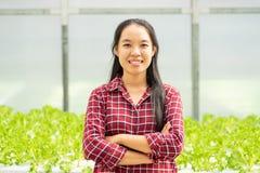 亚裔妇女农夫在菜水耕的农场 免版税库存图片