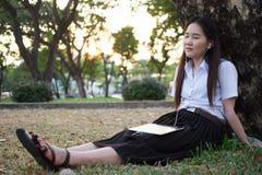亚裔妇女听的音乐 图库摄影