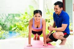 亚裔妇女和个人教练员在体育行使 免版税库存图片