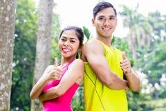亚裔妇女和人在跑步的训练期间 库存照片