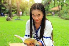 亚裔妇女和逗人喜爱的坐在公园和阅读书的玩具熊 库存照片