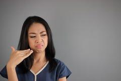 亚裔妇女嗅到某事 库存照片