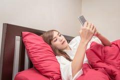 亚裔妇女在上午使用在床上的手机 在床上检查社会apps的亚裔妇女 免版税图库摄影