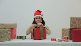 亚裔妇女在与玻璃的桌上,红色盖帽包装礼物和猿 股票录像