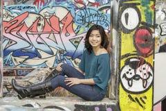 亚裔妇女在公开街道画墙壁的生活方式地点 库存图片