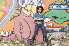 亚裔妇女在公开街道画墙壁的生活方式地点 免版税库存图片