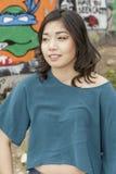 亚裔妇女在公开街道画墙壁的生活方式地点 免版税库存照片