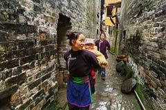 亚裔妇女在农村中国怀有在后面后的婴儿。 免版税库存照片