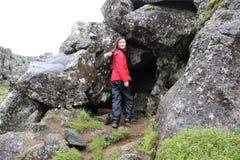 年轻亚裔妇女在冰岛探索洞 免版税库存照片