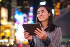 年轻亚裔妇女在城市在晚上 库存照片