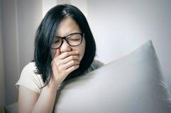 亚裔妇女在她的床上打喷嚏并且咳嗽 免版税图库摄影