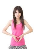 年轻亚裔妇女在她的腹部做心脏形状 库存照片