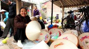 亚裔妇女在市场上的卖帽子 库存照片