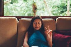 年轻亚裔妇女在放松在有大窗口的沙发的假期时在她后 妇女暑假在巴厘岛 库存照片