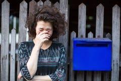 亚裔妇女在有一个蓝色邮箱的篱芭附近站立 哀痛 库存照片