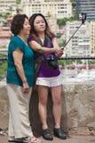 亚裔妇女在棍子做与智能手机的selfie在观点在摩纳哥 库存照片