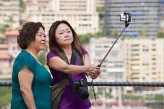 亚裔妇女在棍子做与智能手机的selfie在观点在摩纳哥 图库摄影
