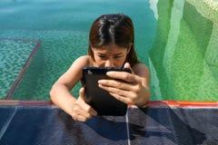 亚裔妇女在游泳池区域的拿着片剂 免版税库存图片