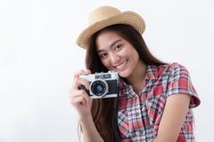 亚裔妇女在白色背景使用一台影片照相机射击 免版税库存图片