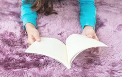 亚裔妇女在紫色地毯在房子被构造的背景中说谎在地板为的特写镜头读了一本书放松时间,在h的业余时间 免版税库存照片