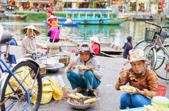 亚裔妇女在街市上的吃和烹调玉米棒子 库存图片