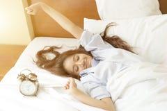 年轻亚裔妇女在设法的床上醒与闹钟 免版税库存照片