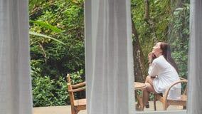 亚裔妇女坐一把木椅子在阳台上有绿色自然背景 免版税库存照片