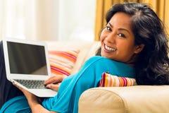 亚裔妇女坐冲浪互联网和微笑的长沙发 库存图片