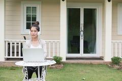 年轻亚裔妇女坐听音乐和使用的椅子 免版税库存图片