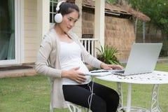 年轻亚裔妇女坐听音乐和使用的椅子 免版税库存照片