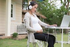 年轻亚裔妇女坐听音乐和使用的椅子 库存照片