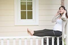 年轻亚裔妇女坐听音乐微笑的阳台 免版税库存图片