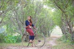 年轻亚裔妇女坐在部落的一辆老自行车在米穿戴 免版税库存照片