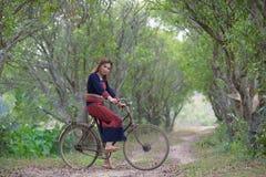 年轻亚裔妇女坐在部落的一辆老自行车在米穿戴 库存照片