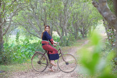 年轻亚裔妇女坐在部落的一辆老自行车在米穿戴 库存图片
