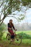 年轻亚裔妇女坐在部落的一辆老自行车在米穿戴 免版税库存图片