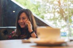 亚裔妇女坐沙发,使用和谈话在巧妙的电话在与咖啡杯和木桌前景的现代咖啡馆 免版税图库摄影