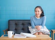 亚裔妇女坐沙发 免版税库存图片