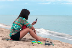 亚裔妇女坐海滩。 免版税库存照片