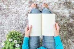 亚裔妇女坐灰色地毯在地板在房子构造背景为的特写镜头读了一本书放松与人为的时间 库存图片