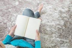 亚裔妇女坐灰色地毯在地板在房子构造背景为的特写镜头读了一本书放松时间,业余时间在 免版税图库摄影