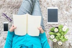 亚裔妇女坐灰色地毯在地板在房子构造背景为的特写镜头读了一本书放松与人为pla的时间 库存图片