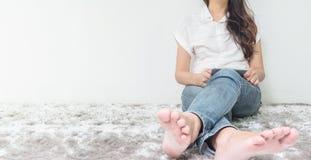 亚裔妇女坐灰色地毯地板有白水泥被构造的背景在房子的角落用途片剂的在她的手上与 库存图片