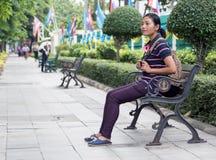 亚裔妇女坐长凳 免版税库存照片
