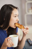 年轻亚裔妇女坐食用咖啡和吃a的沙发 免版税库存照片