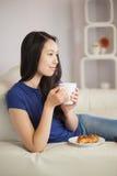 年轻亚裔妇女坐食用的沙发与pastr的咖啡 库存照片