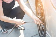 亚裔妇女填装的空气到增加压力车胎的车胎里 图库摄影