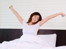亚裔妇女少年在床上醒和放松 免版税图库摄影