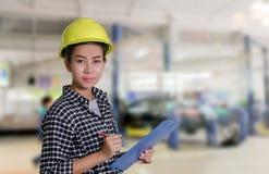 亚裔妇女工程师和技术员技工检查和在一辆汽车的板的inspectingthe名单在汽车修理店的 库存图片